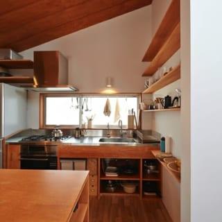 キッチン/東側の大きな窓から光が入るキッチン。シンクの天板はステンレス、木はシナベニアを使用。奥様の要望によりところどころ、「見せる収納」と「見せない収納」を意識して作っているところがポイント。