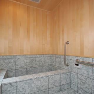 浴槽には伊豆石を、壁にはヒバを採用している。