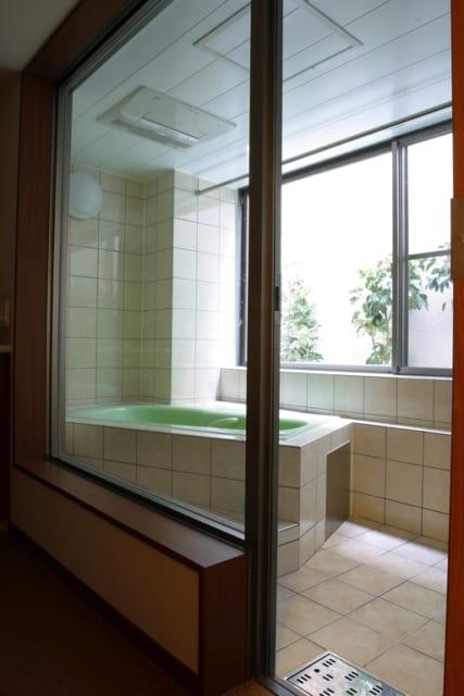 1階の駐車場の奥は風呂場。湿気を逃がすためのドライエリアにも木が植えられ、窓から顔をのぞかせている。浴槽は外を眺めるように斜めに向けた