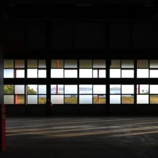 撮影:GEN INOUE  窓~南面/南面の窓を工場内部から望んだ写真。透明ガラスとすりガラスが美しい市松模様になっているのがよく分かる