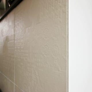 キッチンカウンターの仕上げ材にはレリーフを施した大判タイルを貼った。白と黒を基調とした空間でここだけグレーを採用。無彩色で統一感を保ちつつアクセントを添えた