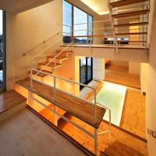 1.5階キッチン~2階/1階の玄関ホールと2階の居間をひと目で見渡せるキッチン。階段はスケルトンで、より見通しがいい。2階への階段は、階段板の1枚を長く延ばして柵の一部に。娘さんはここをカウンター代わりにして、椅子のように床に座って本を読むのが好きだそう