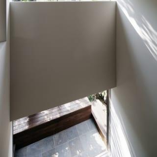 1階 吹抜けを見下ろす/土間の上部は壁の隅まで開いたハイサイドの窓があり、明るい光がさんさんと降りそそぐ。ウッドベンチ付きのテラスの床は、土間と同じ石のスレート。少しサビが入っていて、独特のニュアンスを醸す。汚れやキズが目立ちにくく使い勝手は抜群