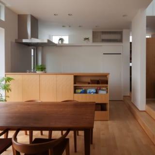 ダイニング~キッチン/キッチンは、ダイニングテーブルと向かい合うように設計された対面型。食器棚やパントリー、冷蔵庫スペースには壁と同色の引戸をつけた。生活感のあるものを隠せて見た目にも美しいだけでなく、必要に応じて開け閉めすることで汚れにくいというメリットも