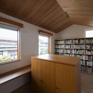 2階書斎/前の住まいから持ってこられた書棚を仕切にして、窓や本棚などを左右対称に配した書斎。切妻屋根の形を活かして空間に広がりを持たせた天井には、色味の美しいアルダー材を用いた