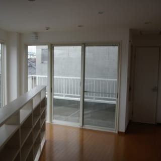 """3階 家族室/3階の階段をのぼりきったところを広くとり、思い思いにくつろげる""""家族室""""とした。このスペースは南東に面するため日当たりは抜群。K邸の南東方向の中で最も眺望が抜ける場所で見晴らしもよい。階段を見下ろす手すりを造り付けの書棚にしたのは、読書好きなKさん一家のためのアイデアだ"""