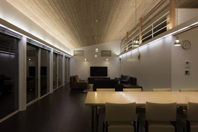ダイニング・リビング/窓の上辺部分にはアップライトがあり、電球光が白いオイルステインで塗装した天井にほどよく反射。天井全体がやさしい明るさを帯びてゆったりとくつろげるが「手もとはもう少し明るい方がいいので」と、谷内田さんはテーブルまわりにペンダントライトも設置した。写真右上にはロフトもあり、視線の抜けによって広い空間をより広く感じさせる