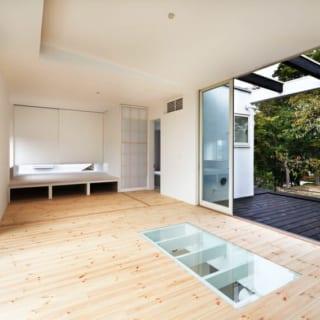 2階居間/居間の床の一部はガラス張り。下を覗くとちょうど水盤が見える。ふんだんに入る陽光がこのガラス部分を通して そのまま1階の水盤に届き、キラキラと美しい光が舞う。写真奥の一段上がったスペースは子ども部屋やゲストルームとして使用。その横の扉の先にはバスルームなどがある