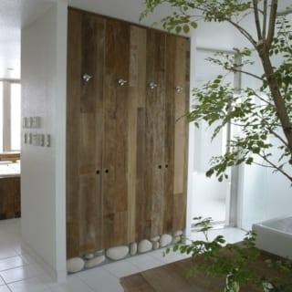 6階自宅 水まわり/大小さまざまなグリーンの鉢植えをレイアウトした洗面スペースは、朝晩の支度が楽しみになる癒しの空間。味わいのある古材を用いた洗面台や収納扉とあいまって、森の中にいるかのよう。ここは収納を介してベッドスペースとつながっており、動線もよい