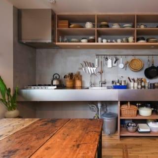 2階 キッチン/店舗にも調理スペースはあるが、ずらりと並ぶ調理器具から料理が仕事でもある奥さまの腕前がうかがえる。上下の収納は造り付け。合板の切口を見せてニュアンスを出している。道具をかけたバーは夫妻の希望でつけたもの。使いたいものが見やすく、かつ、手にとりやすいキッチンだ