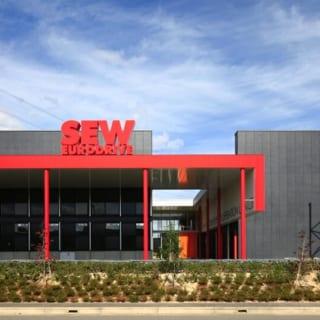 撮影:GEN INOUE  エントランス/写真右手の事務棟と左の工場に挟まれた、奥のオレンジのドアがエントランスとなる。上までガラスを設置して、建物のはざまでも十分に光を取り入れられる造りになっている