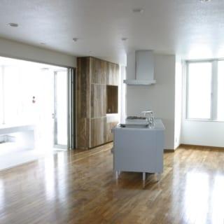 6階自宅 キッチン~サンルーム/写真左、キッチンの背後は、屋上庭園へ続くタイル張りのサンルーム。テーブルを置けるゆったりとした広さの半戸外空間だ。ここから入る日差しは室内の明るさにも大きく貢献