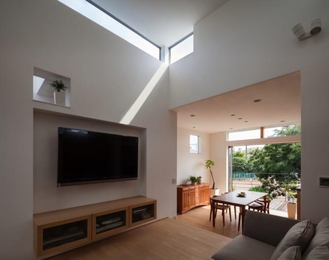 リビング/テレビ上部にはハイサイドライトをL字に配し、陽の光が白い壁に反射することで、光を部屋全体に行き渡らせるような仕組み。造りつけのサイドボードは、今後映像機器が増えてもいいように余裕を持たせた