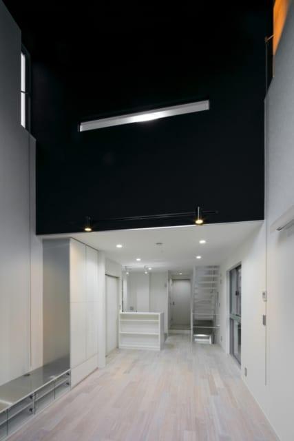 吹き抜けの壁一面に黒のアクセントクロスを使用。横長のスリットからは3Fの子ども部屋の灯りが漏れる