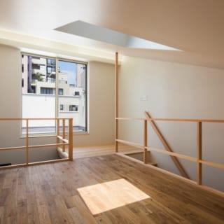 ロフト/寝室として使用。天井には、青空や星空を眺められるトップライト。大きな窓の向こうには広々したテラスがある。燦々と入る日差しは吹抜けやグレーチングを通して2階にもおよぶ