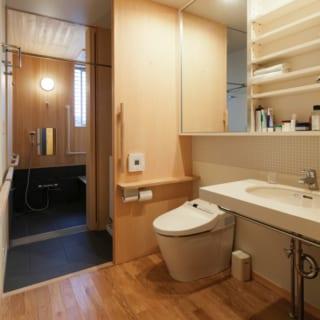 1階洗面室・トイレ・バスルーム/ヒノキの素材感が和の洗練された雰囲気を醸す水まわりは、車椅子でも動ける広さ。バスルームの天井や壁はヒノキ板張り、床の黒いタイルは冷たさを抑えたタイプを使用。入浴後に窓を開けて換気すれば、特別なメンテナンスなしでもヒノキの劣化やカビ発生の心配はないそうだ