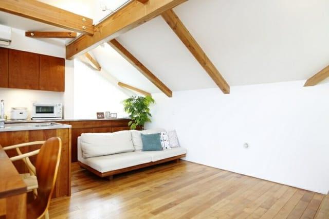 2階 リビング/写真右、北の天井は高度斜線制限の関係で低くしたが、南の高い天井や東西の窓のおかげで圧迫感はゼロ。むしろ空間に包まれている安心感があり、ゆったりくつろげるリビングになった