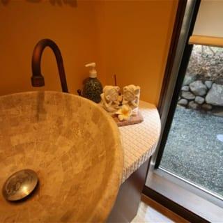 トイレもすこし開放的にしました。お隣の緑を借景するよう窓を配します。 手洗いボールや化粧鏡は取り寄せました。