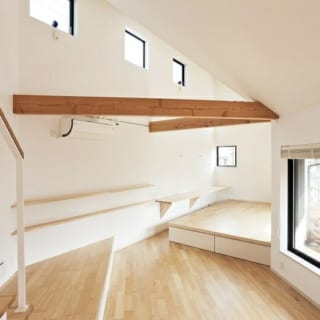 1階 小上がり/勾配の一番急な東側にあたる。左のテーブルはお子さんが宿題できるように設けられた。また、小上がり・左の階段最下段・右の窓枠は高さがそろえられていて、腰をかけて自然なコミュニケーションをとれる
