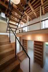1階と2階をつなぐ階段中央から室内を望む。1階ホールにある2つの本棚は壁をくり抜いて造作したもの