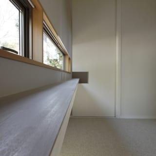 子世帯 主寝室/北の壁に沿って横長の窓とカウンターを設置。カウンターは隣の書斎まで続く。写真右手方向に出入口があり、主寝室を出ると通路を挟んで子ども部屋。子ども部屋は主寝室側をすべて引き込み戸とし、オープンに使えるようになっている