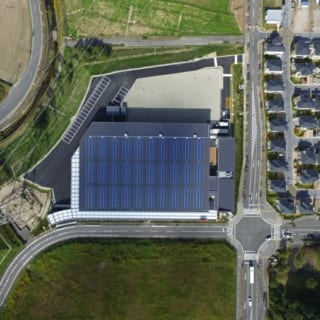 撮影:GEN INOUE  航空写真/日射を最も多く受ける屋根には、厚さ50mmの断熱材のほかにも、太陽光パネルを設置。発電と屋根面の日除けを兼ねている