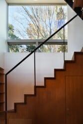 階段を上り下りするたびに、さりげなく緑の木々が目に入ってくるよう演出。階段下には収納を設けている
