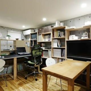 地階 ワークスペース/書物や模型がぎっしり置かれた日部さんのワークスペース。地階は鉄筋コンクリート造なので、内装もコンクリート打ち放しの洗練された印象に。疲れたら2階に上がってひと休み。家の中でオン・オフがつけられ快適だが、オフィスを移転した場合は子ども部屋などにしてもいい