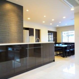 パーティスペースとしても活躍するダイニングキッチンも充実の収納を。天板奥行きが広くとれることからオープンキッチンを採用し、天板下を収納にフル活用。収納扉は鏡面仕上げで床の大理石とテイストをそろえた