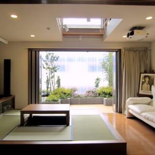 畳とソファのあるリビング。左手にスクリーンをおろして、ホームシアター用のスピーカーを使えば、家で見る映画も迫力満点