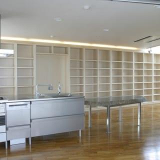 6階自宅 LDK/テーブル一体型のキッチンはクールなステンレス製。四角い部屋の対角線に沿って斜めに配し、表情豊かな空間になった。写真奥は施主さまの膨大な書物を収める本棚で、キッチンと平行させてレイアウト。本棚の背後はベッドスペースと水まわり