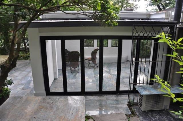 """外観 折り戸/緑あふれる庭を間近に感じられる、大きなガラスの折り戸。テラスハウス内と庭の境界が曖昧な半戸外空間として、""""室内と屋外のいいとこどり""""ができる"""