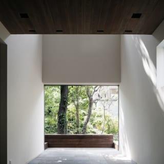1階 土間から外を見る/土間からテラスへの開口は大きな掃き出し窓。左右に壁を残していないので見た目がとてもすっきり。土間が屋外とひと続きの空間になり、開放感をもたらす