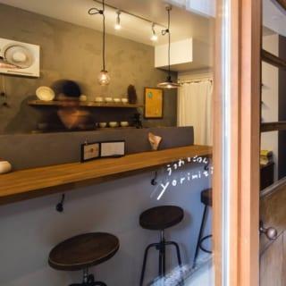 1階 店舗入口/建物の横にある細長いアプローチを入ると、奥さまが営むうつわと軽食の店がある。出入口は正面の大通り沿いにつくるプランも考えたが、「自宅兼店舗なので、少し入りにくさも欲しい」という奥さまの希望で側面に配置した