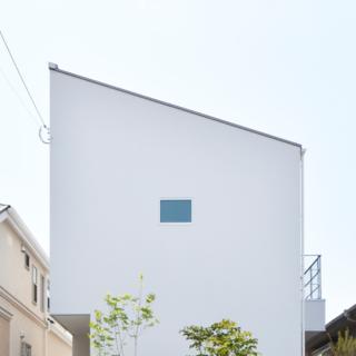 外観/北側、アプローチからの写真。片流れ屋根と白壁がシンプルで洗練された印象を与え、個性を放ちながらも住宅街になじんでいる