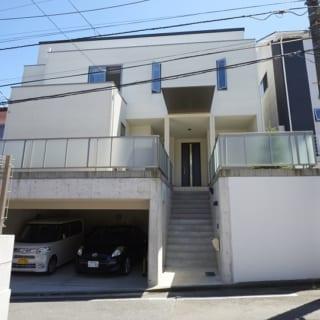 正面からの外観。通りに面した北側の天井が高くなっているため、より大きな家という印象に。駐車場と階段の間には、雨に濡れずに庇の下へ行けるドアもつけてある。