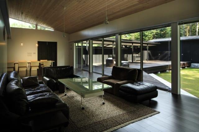 リビング・ダイニング/40畳を越える広々した憩いの場は床暖房が入っており、冬の滞在も快適。庭に沿って何枚ものガラス窓が連続し、心地よい開放感がある。この窓からはそのままテラスに出られるので屋外との一体感も十分。親族や仲間とのホームパーティーに大活躍する空間だ