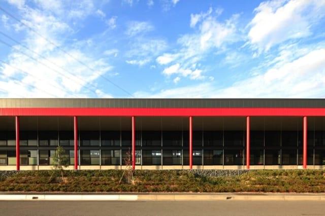 撮影:GEN INOUE  ファサード~南面/コーポレートカラーでもある赤に塗られた柱。鳥居、コリント式の柱など、整然と並んだ赤い柱はさまざまなとらえ方ができて面白い