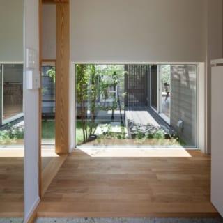 玄関の扉を開けるとまず目につく正面の中庭。すべてを見せず、奥ゆかしさを感じさせる。和室(左手)との連続性にもこだわった。