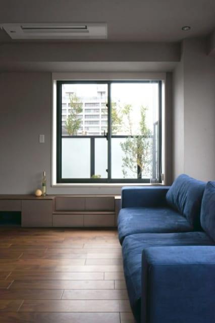 リビング/バルコニーへ出る窓は下枠が高いため、造り付けのテレビボードは階段も兼ねている。空間の印象を大きく左右するソファや電動ブラインドは、伊藤さんも一緒に見に行って選んだ