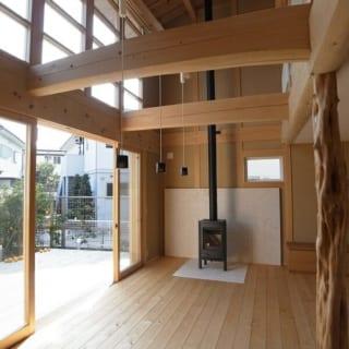 サンルーム/木の梁をそのまま出すことで木の風合いを生かした吹き抜け空間。窓を開け放てばウッドデッキとリビングがひと続きになる