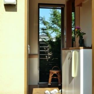 玄関/玄関を入ると窓越しに中庭が見え、視線が抜けて広がりを感じられる。高齢のお母さまのことを考えて上がり框は低めに設計し、通路には手すりも設置