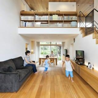 1階リビング・ダイニング/右の階段の途中にお子さんたちが遊ぶ中2階があり、階段をのぼりきった先が将来の子ども部屋。2階の左奥には主寝室がある。リビングを見下ろす2階通路は書斎コーナーとして活用