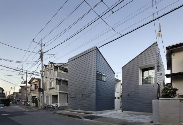繁田諭   【写真9】A棟 外観/ひとつの敷地に2戸のL字型の家をうまく収めている。お互いの視線が気にならないよう家の配置をずらし、窓の位置も考えた。B、C棟と同じ黒いガルバニウム鋼板の外壁だが、それぞれの印象が異なる