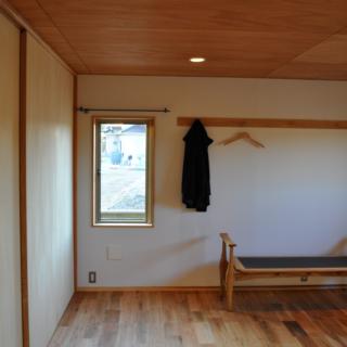 主寝室/天井と床の木の風合いを引き立てる砂漆喰の壁