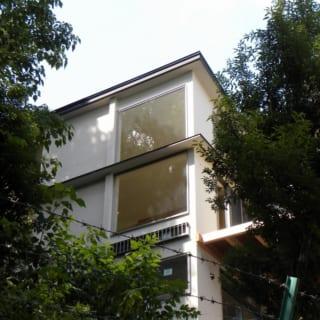 南東から見たWさん邸の外観。外壁は石灰モルタルの漆喰を採用。隣接する公園の緑とのカラーマッチングを意識して白で統一した。構造は木造在来工法。