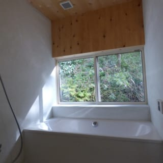 浴室/浴室の壁はセメント、天井はカビに強く香りのよいヒバ材を使った。窓いっぱいにパティオの緑が広がる造りは旦那さまのリクエスト。「バスタブは、肌ざわりがよく見た目にも美しいドイツのホーロー製を採用しました