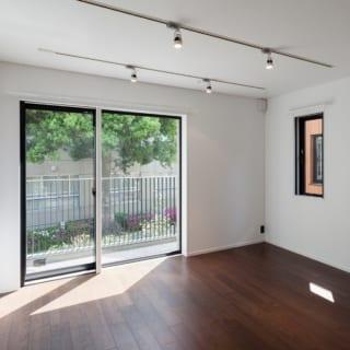 賃貸住戸 居室/賃貸住宅では珍しい重厚感のある床は、1階はピンカドの無垢材、湿気が気になる地階はウォルナットの無垢と合板の複合材を用いている。ほか、照明はダウンライトやスポットライト、エアコンは天井に埋め込まれたカセット式を採用。室内の面に凹凸がなく、すっきりとした印象に