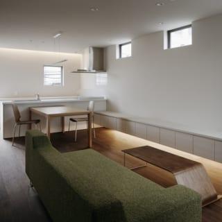 2階 LDKの入口から/写真奥のキッチンの背後には床から天井までの開口を設けてある。階段をのぼりきるとこの窓が視界に入る仕掛け。空間をより明るく、広く感じられる。写真右の南の方角は隣家が密接しているため大きな開口は避け、複数のハイサイド窓で採光を確保した