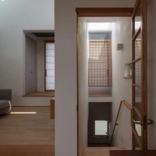 階段上/明るさを感じられるよう、階段上にはトップライトを設けた。写真奥の和室との仕切りも木製の格子にし、気配感が伝わる設計とした